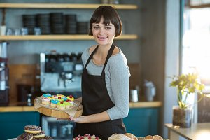 Portrait of waitress holding cup cake on tray in café