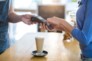 Customer making payment through payment terminal at counter in café