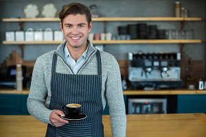 Portrait of waiter holding cup of coffee