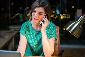 Businesswoman talking on mobile phone while working on laptop