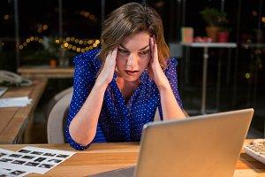 Stressed businesswoman sitting at her desk