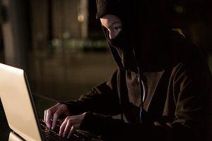 Woman in balaclava using laptop