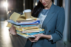 Businesswoman carrying stack of file folders while using mobile phone