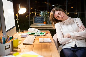 Tired businesswoman sleeping on chair