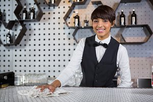 Smiling waitress cleaning bar counter