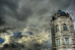 Modernist tower under cloudy sky