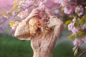Beautiful young woman standing at blossoming tree in the garden