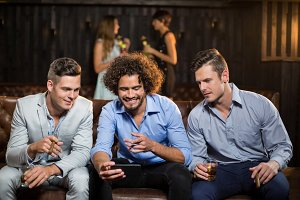 Three happy friends looking at mobile phone while having cigar and whisky