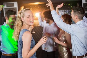 Woman holding glass of champagne while dancing with friends