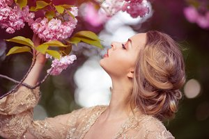 Beautiful sexy adult girl standing at blossoming tree in the garden