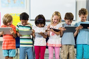 Smiling schoolchildren using digital tablet