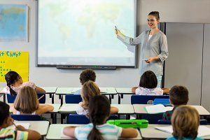 Teacher teaching schoolchildren using projector screen