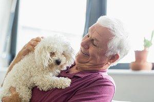 Senior man holding a dog