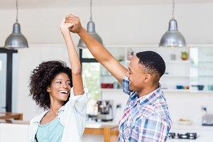 Happy couple dancing in kitchen