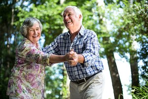 Happy senior woman dancing with husband against trees