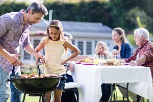 Father and daughter at barbecue grill while family having lunch in background