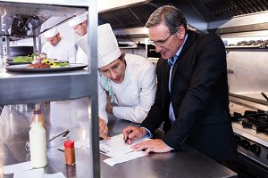 Male restaurant manager writing on clipboard while interacting to head chef