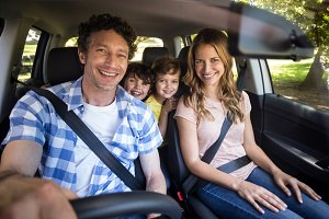 Smiling family sitting in the car