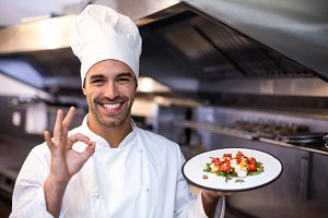 Handsome chef showing ok sign and meal
