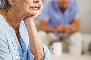Worried senior woman sitting on sofa