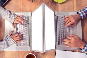 Cropped image of hands using laptops