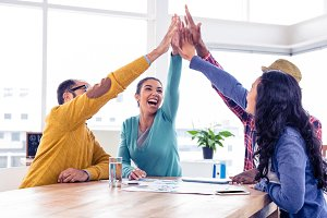 Cheerful business team doing high five in creative office