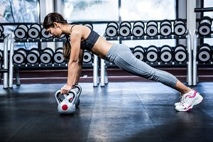 Fit woman doing push ups with kettlebells