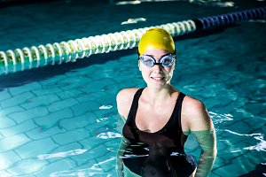 Fit smiling swimmer woman standing
