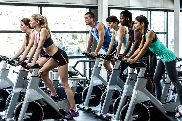 Fit people working out at spinning…