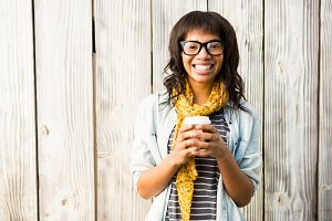 Smiling casual woman posing with glasses while holding coffee