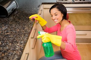 Smiling brunette cleaning kitchen counter