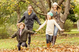 Smiling young family running into leaves