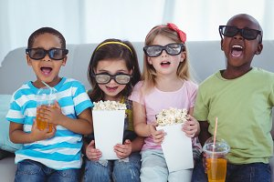 Happy kids enjoying popcorn and drinks while sitting