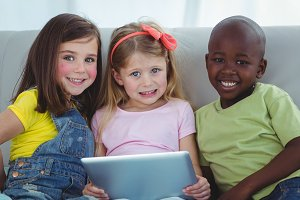 Happy kids sitting together with a tablet