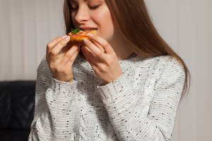 woman is eating pizza