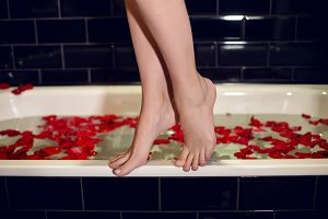 girls feet standing on the edge of the white tubs