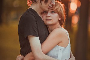 guy and the girl embracing on a background of nature park