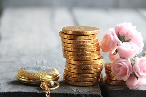 Business or finance concept. Stacks of golden coins and roses.
