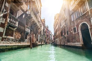 Small venetian canal and old brick walls with vintage traditiona