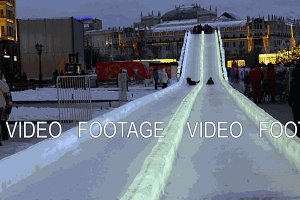 Christmas Ice slide for children riding in the evening in Moscow