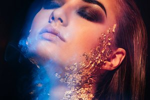 portrait of beautiful girl with gold on his face, made in mixed light, ice and fire
