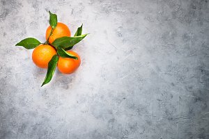Tangerines fruit on grey concrete table.