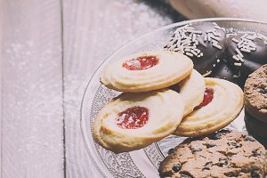Various types of biscuits on glass tray next to a roller on wooden table. Vertical shoot