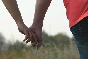 Young couple joining hands outdoor. Man and woman taking arms on nature background. Male and female hands comforting and stroking each other. Symbol of love and devotion. Romantic outside. Close up