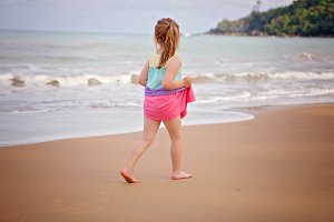 Little girl walking on beach