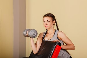 Girl exercise biceps with dumbbells