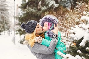 Mother and daughter kiss winter