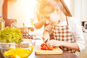 Young teenage girl cook together with her family