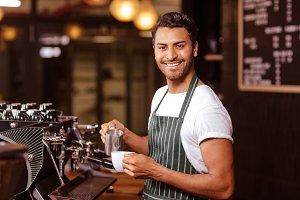 Handsome waiter adding milk to coffee
