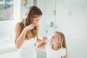 Smiling mother and daughter brushing teeth